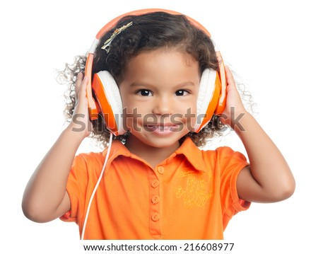 Small afro american girl with curly hair listening music on bright orange headphones - stock photo