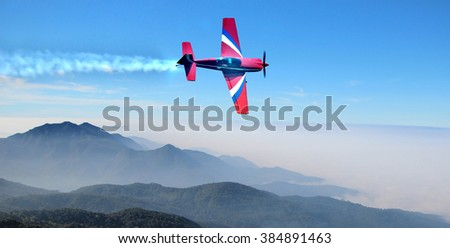 Small airplane in the sky above the mountains - stock photo