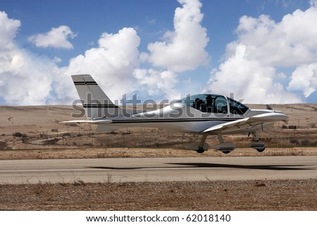 Small airplane landing in a small desert airport - stock photo