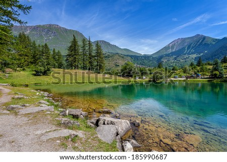 Small alpine lake Laux in the valley among mountains in Alps, Northern Italy. - stock photo