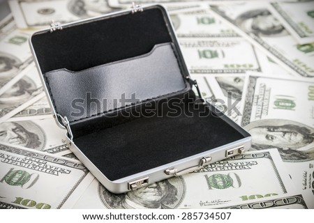 small aluminum case for the dollar. Focus on the handle of the case - stock photo
