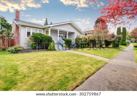 Small American home with light exterior and a large grass filled lawn. - stock photo