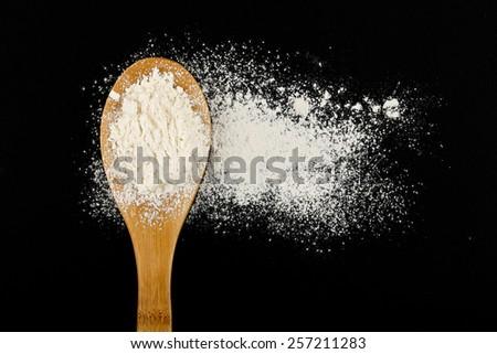small amount flour on black background - stock photo