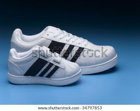 Small and big sports shoes - stock photo