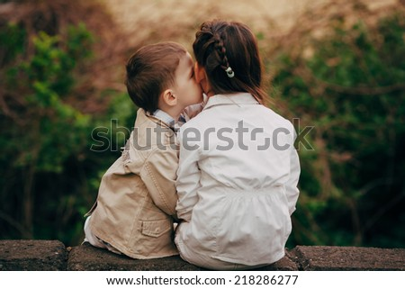 Small and pretty child fell lovely and happy it`s  first kiss - stock photo