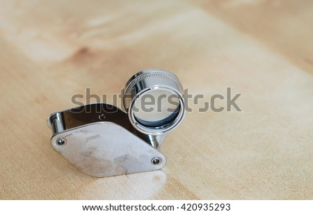 Small and unique magnifier on wooden background - stock photo