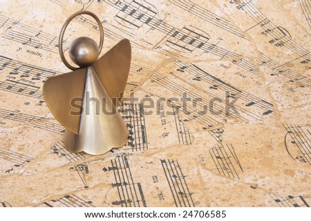 Small angel on a sheet music as background - stock photo