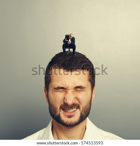 small angry boss screaming at big worker over grey background - stock photo