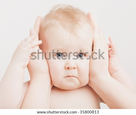 Small angry boy with hands on ears - stock photo