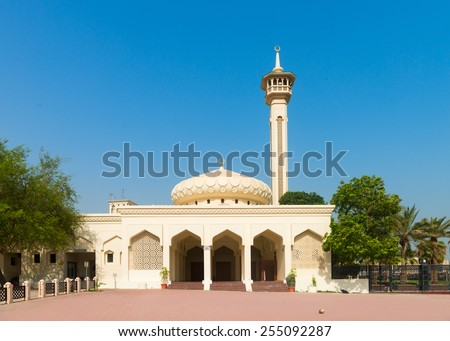 Small arabic light yellow mosque with one minaret under clean blue sky - stock photo