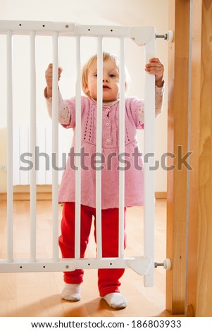 Small baby approaching safety gate of  stairs - stock photo