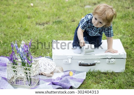 Small baby boy with blond hair in blue checkered shirt and jeans sitting on white vintage briefcase with bucket cage purple field flowers and plaid on green grass outdoor copyspace, horizontal photo - stock photo