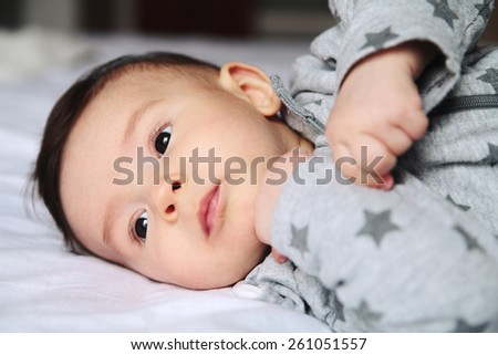 Small baby crawling on the bed in white room.On his face interest and wondering.European.Baby surprised. - stock photo