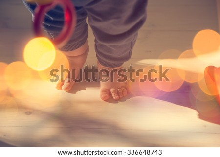 Small Baby Feet on Wooden Floor. First Steps Concept. Shallow Depth of Field. Toned Photo with Bokeh and Copy Space. - stock photo