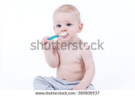 Small baby is training eating with plastic spoon - stock photo