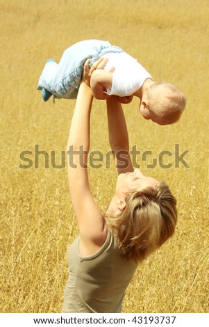 Small baby with mother outdoors. Summer Time. - stock photo
