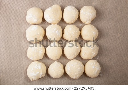 Small balls of dough with flour for pizza or cakes and scones on baking paper . Shallow depth of field - stock photo