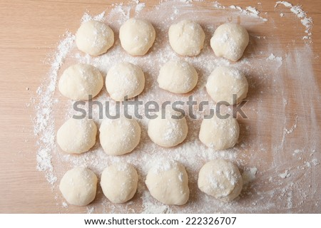 Small balls of dough with flour for pizza or cakes and scones. Shallow depth of field - stock photo