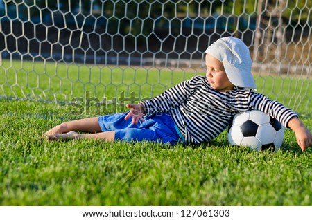 Small barefoot boy in a cap lying relaxing on the green grass in the goalposts with his arm draped over a soccer ball - stock photo