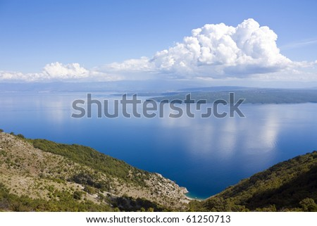 Small bay on croatia island cres, view to island krk with some clouds on sky - stock photo