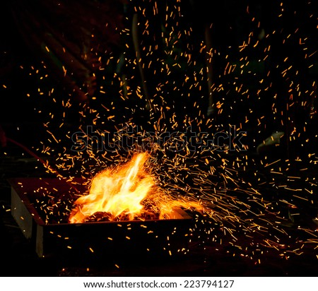 Small BBQ on fire with burning charcoal and flying sparks - stock photo