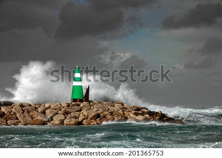 Small beacon on a pier on the storm background - stock photo