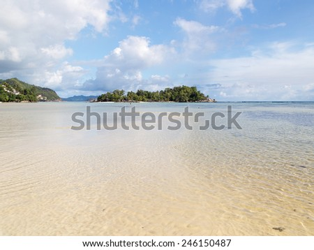 small beautiful tropical island with palm trees and clean salt water Indian Ocean, Seychelles - stock photo