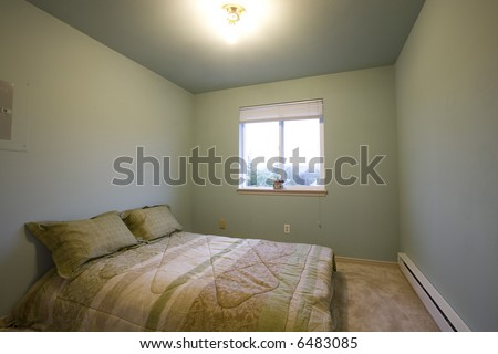 Small bedroom with a window - stock photo