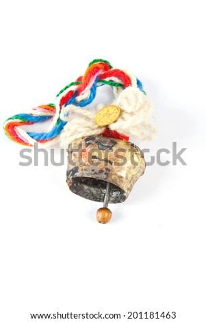 Small bell cow decorated with colorful woolen threads on a white background - stock photo