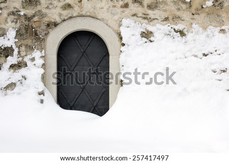 Small black iron castle door, backdoor, covered with snow. - stock photo