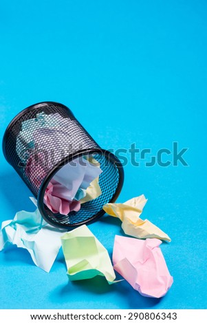 Small black trash bin with crumpled color paper inside over the blue background - stock photo