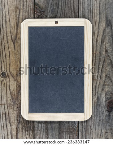 Small blackboard chalkboard hanging on wooden background - stock photo