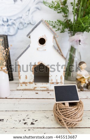 Small blackboard with hemp rope on top of vintage white cabinet - stock photo