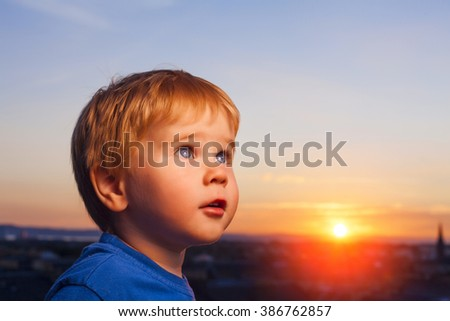 Small blond blue eyes boy expressing excitement over beautiful sunset.  - stock photo