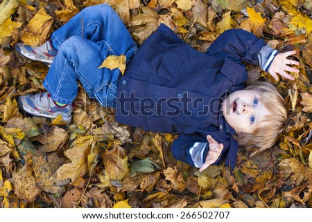 Small blond boy with blue eyes lays on bed of autumn fallen leaves with open mouth - stock photo