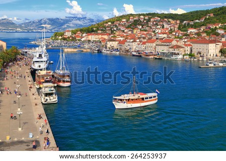 Small boat carries tourists to old Venetian town near the Adriatic sea, Trogir, Croatia - stock photo