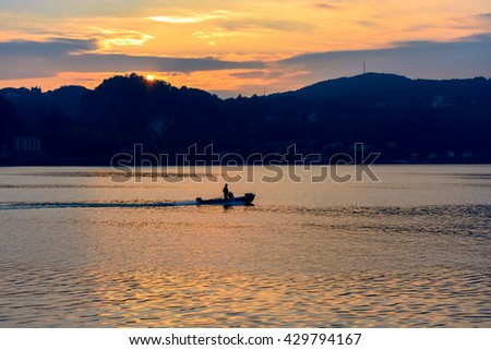 small boat floating on the water at sunset against the backdrop of mountains and the setting sun. Italy, Arona. - stock photo