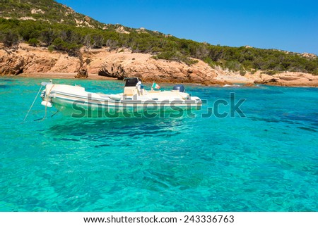 Small boat in turquoise clear sea - stock photo