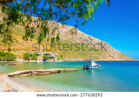 Small boat moored in peaceful bay  with clear sand, Greece - stock photo