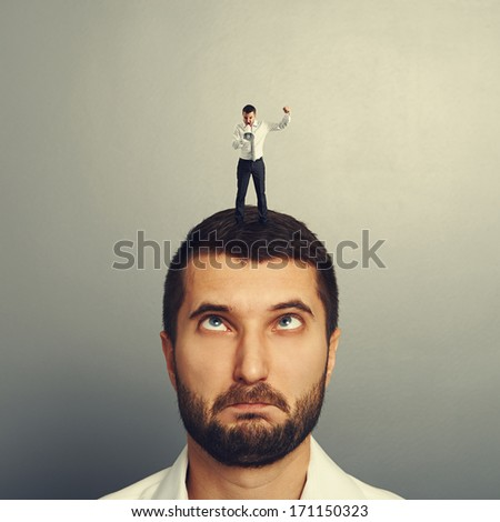 small boss standing on the head and screaming at foolish worker - stock photo
