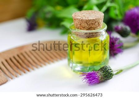 Small bottle of burdock oil  - stock photo