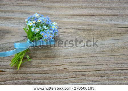 Small bouquet of blue forget-me-not flowers, tied a blue ribbon, on the background of old wooden plank - stock photo