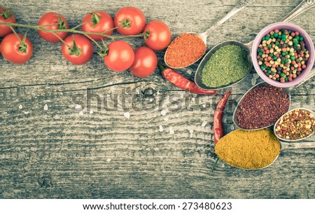 Small bowl and antic metal spoons with different kinds of spices, bunch of cherry tomatoes, sea salt and red hot chili peppers on old wooden board. Selective focus.Toned. - stock photo