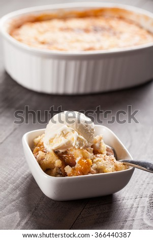 Small bowl of freshly served peach crisp with scoop of ice cream on top - stock photo