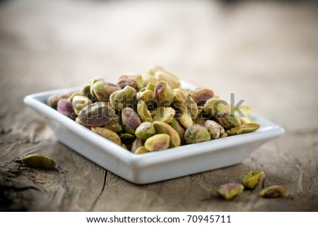 Small bowl of pistachios on wooden table - stock photo