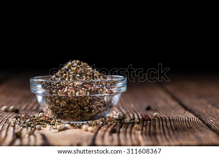 Small bowl with crushed Peppercorns on vintage wooden background - stock photo