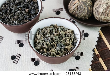 Small bowls of dry green tea leaves and small balls bundle of dried tea leaves  on Japanese pattern tablecloth - stock photo
