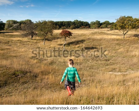 small boy alone walking in dune landscape with grassland,  blue sky and trees - stock photo