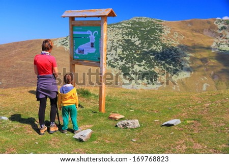 Small boy and his mother near information panel on the mountain trail - stock photo