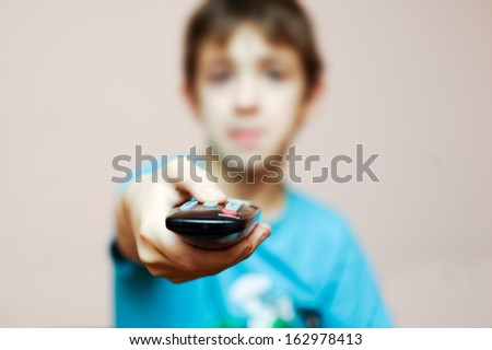 Small boy and TV remote control - stock photo
